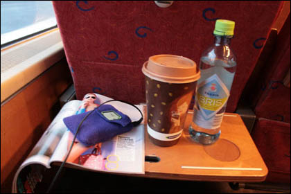 In a train with a mag, ipod, water, coffee